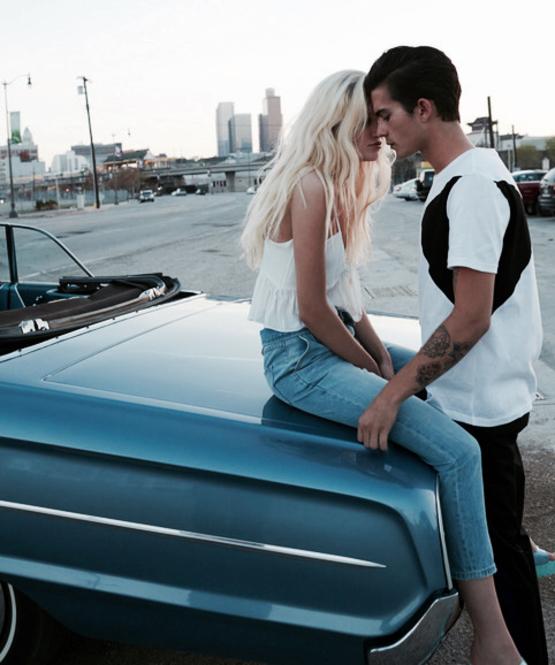 Chico besando a una chica mientras ella está sentada en el cofre de un carro