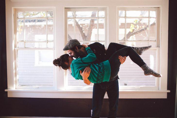 Hombre cargando a una chica para besarla mientras están en la sala de una casa
