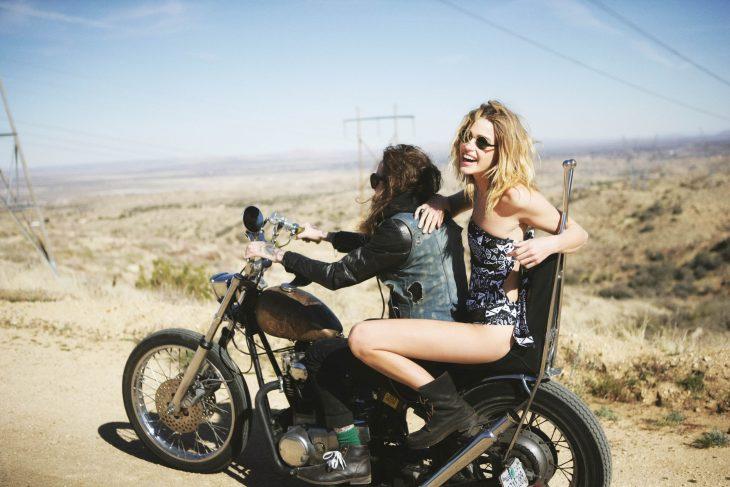 Chica en una motocicleta con un chico mientras van por la carretera
