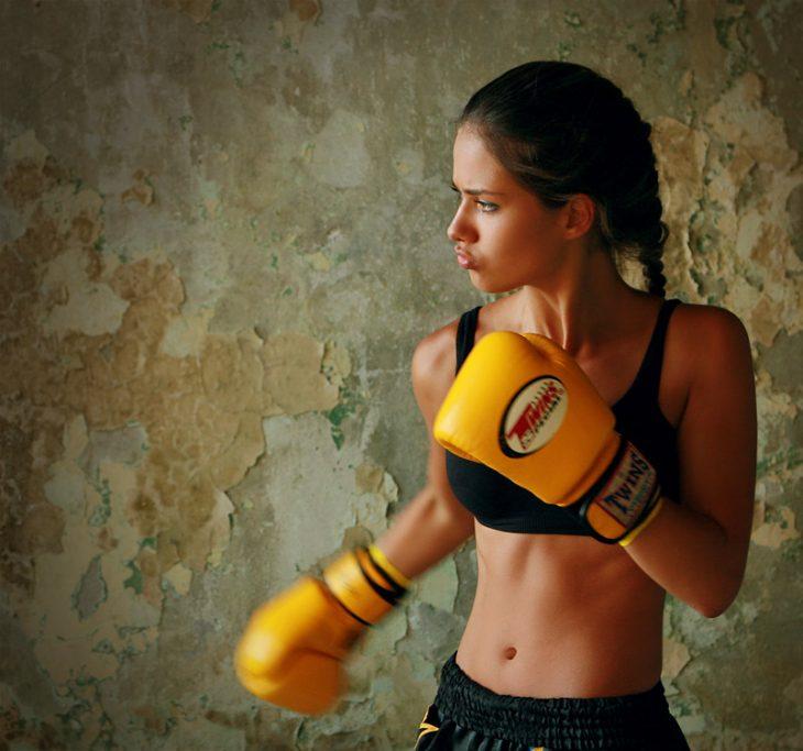 Chica usando unos guantes de box amarillos para luchar