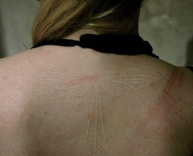 espalda de una chica con un tatuaje de tinta blanca que es una libélula