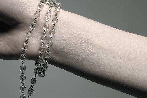 muleca de una chica tatuada con un copo de nieve