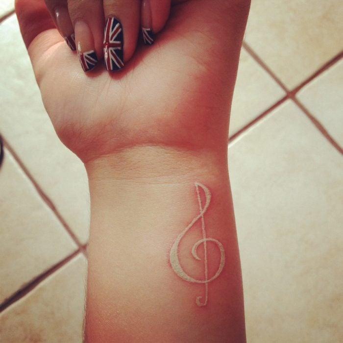 Tatuaje con tinta blanca en forma de letra de música
