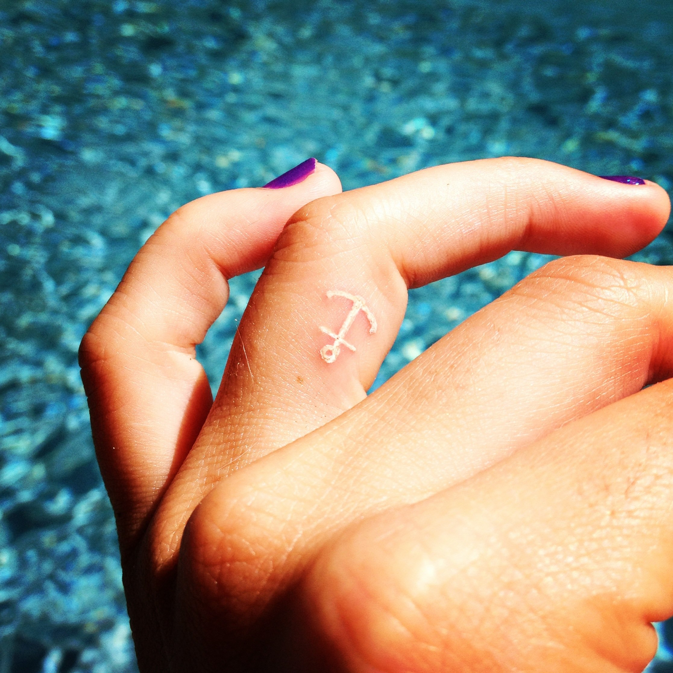 Tatuaje creado con tinta blanca en forma de ancla puesto sobre el dedo medio