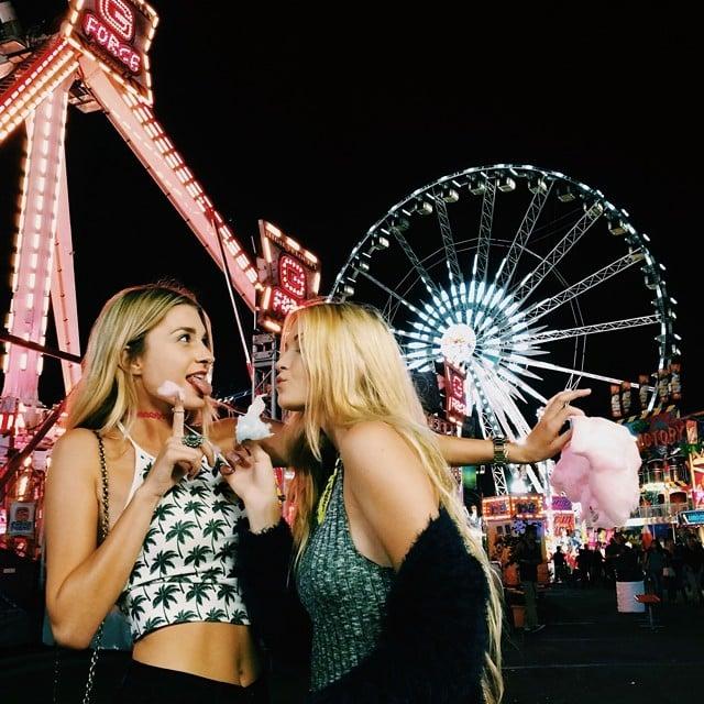 Chicas comiendo algodón de azúcar mientras están en una feria