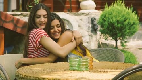 Chicas abrazadas meintras están sentadas frente a una mesa