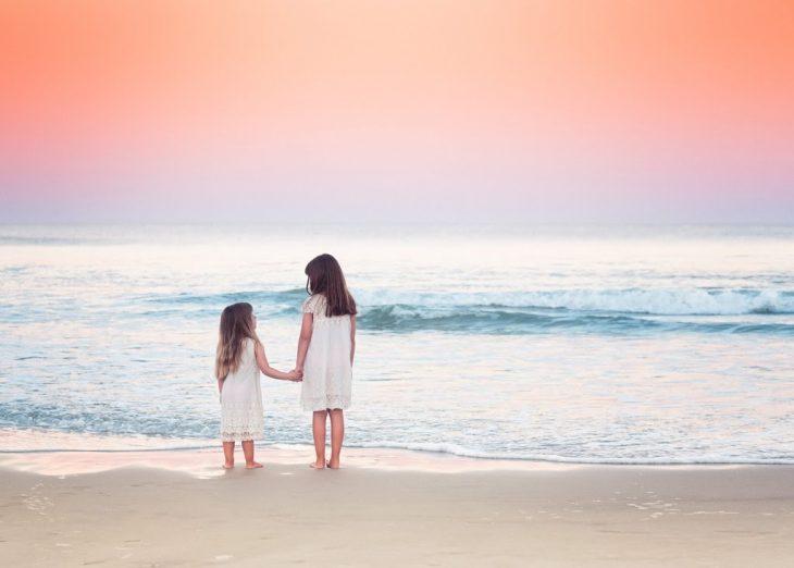 Hermanas abrazadas en la paya viendo el mar