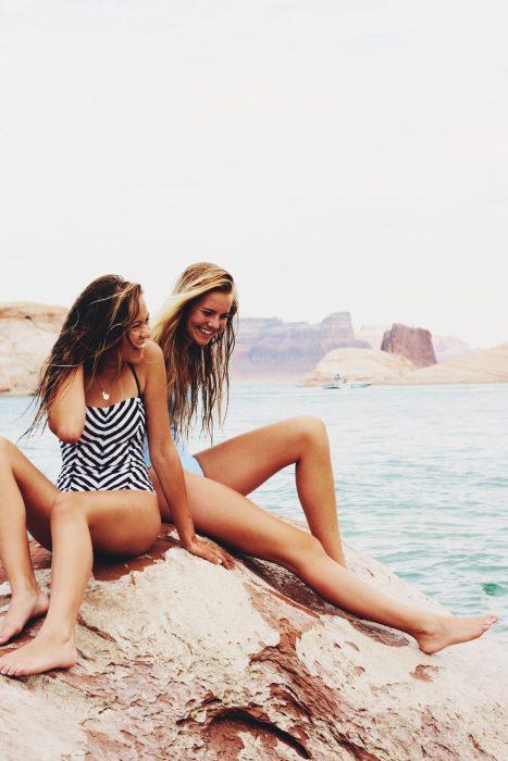 Chicas en la playa sentadas en una roca viendo hacia el mar