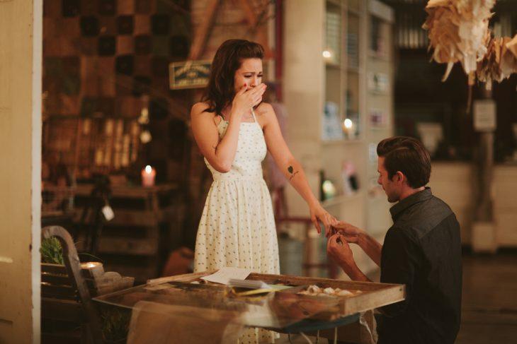Novio sobre una rdilla pidiendole matrimonio a una chica mientras están en un restaurante