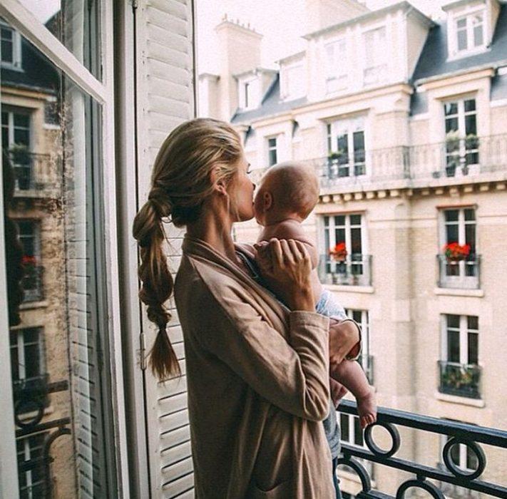mujer sosteniendo a su bebé mientras están en el balcón