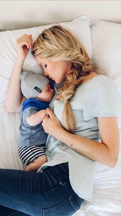 mamá recostada junto a su bebé en la cama
