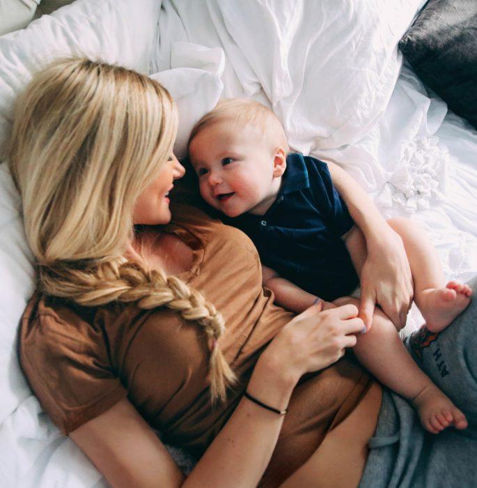 Mamá recostada en la cama junto a su bebé