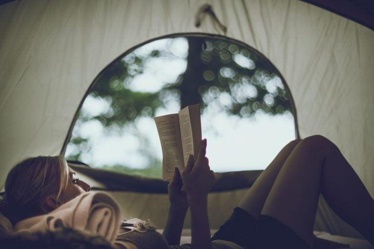 chica leyendo adentro de casa de campaña