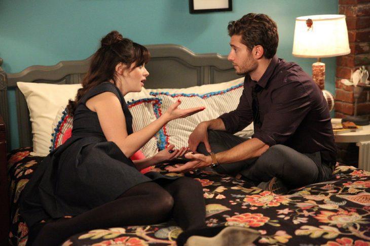 Escena de la serie new girl chicos conversando en la cama