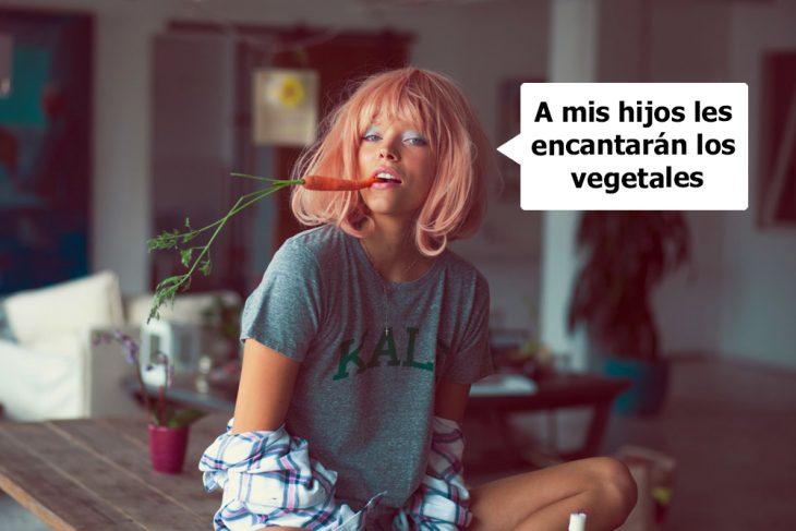 Chica sentada en una mesa comiendo zanahorias