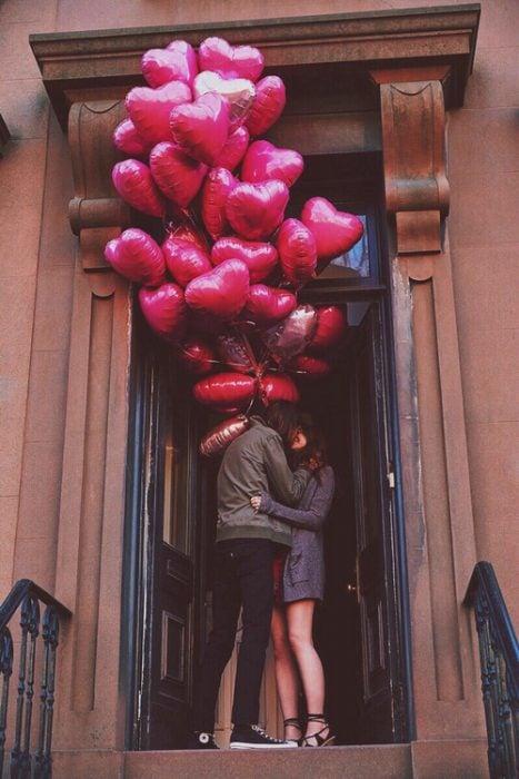 Chico con globos de corazón besando a una chica