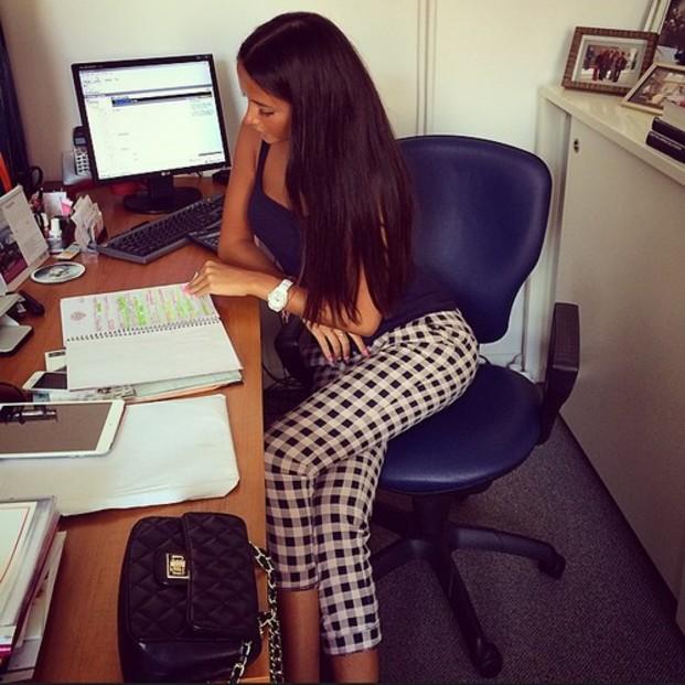 chica sentada frente a un escritorio revisando cosas en una libreta