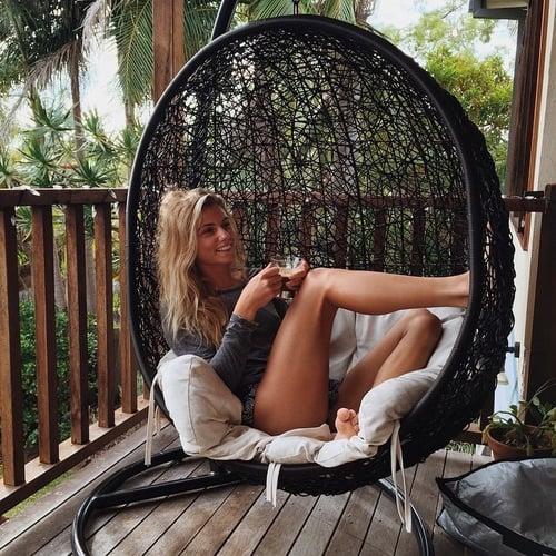 Chica sentada en una hamaca bebiendo café y sonriendo