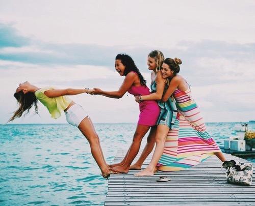 Chica sosteniendo la mano de otras tres porque va a caer en el mar