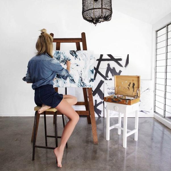 Chica sentada pintando sobre un lienzo en un caballete