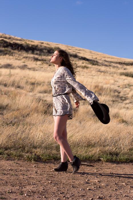 Chica parada sobre tierra con los brazos extendidos hacia atrás