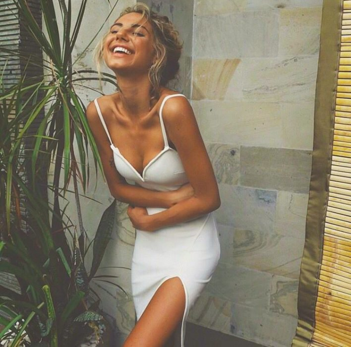 Chica usando un vestido blanco mientras se abraza a si misma