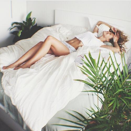 Chica recostada en una cama sonriendo