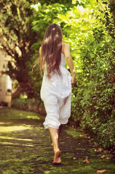 Chica corriendo a través de un jardín