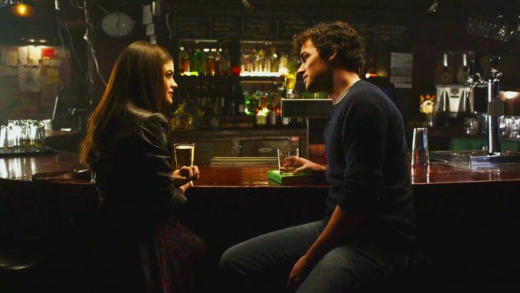 Escena de la serie pretty little liars pareja de novios hablando en la barra de un bar