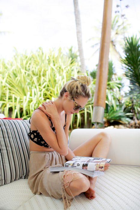 Chica sentada en un sofá leyendo una revista
