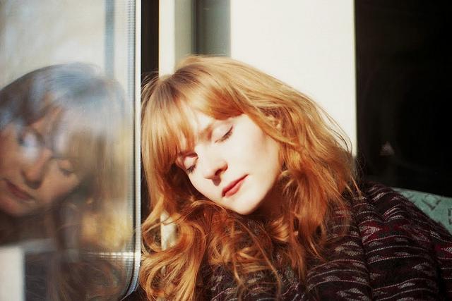 chica pelirroja recargada frente a ventanal con ojos cerrados