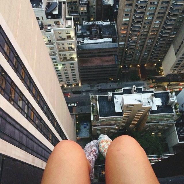 chica con piernas colgando orilla de un edicio