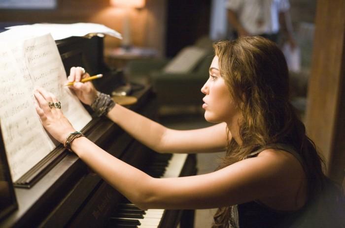 chica anotando notas sobre un piano