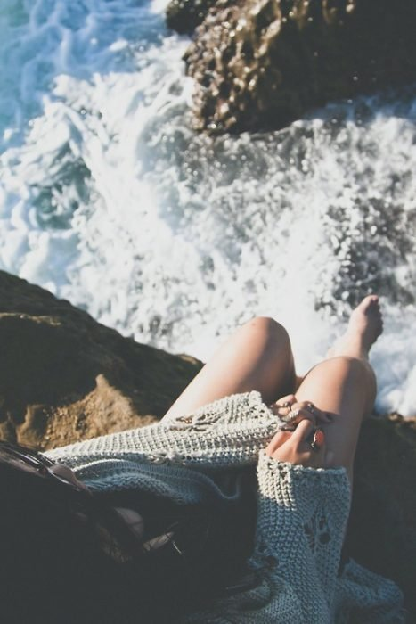 chica sentada en orilla de un acantilado