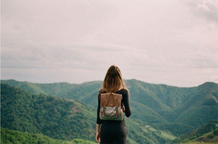foto chica de espaldas con mochila en un monte