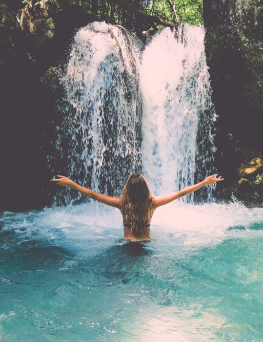 chica de espaldas frente a cascada