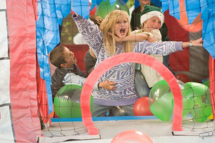 Escena de la película four chritsmas chica jugando con niños en una alberca de pelotas