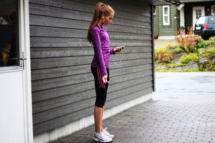 Chica con ropa deportiva y sosteniendo su ipod para escuchar música