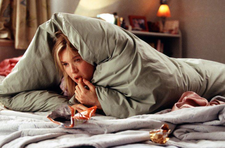 Escena de la película el diario de bridget jones chica recostada en la cama con un cobertor sobre su cuerpo