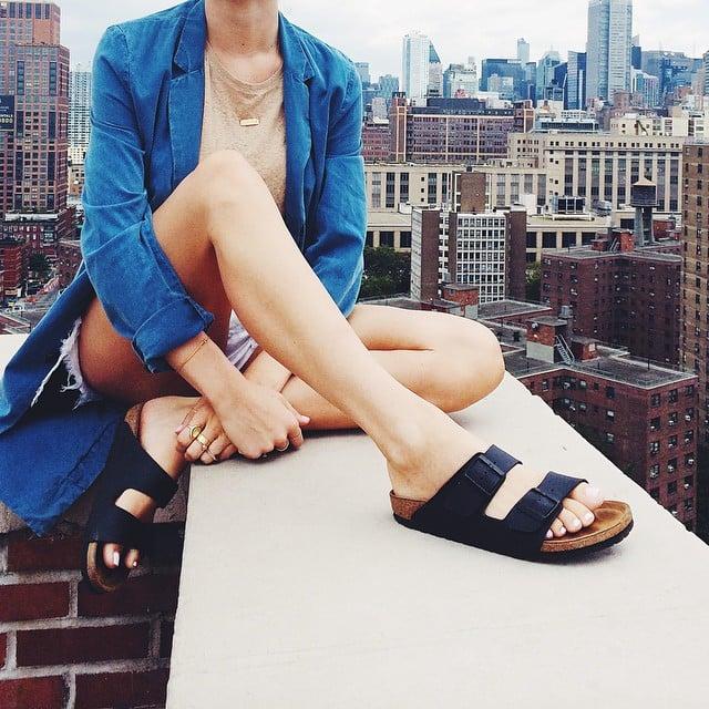 Chica sentada en una azotea usando unas sandalias birkenstock
