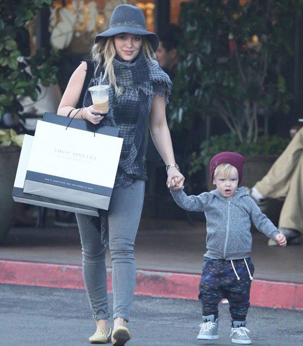 Hilary duff caminando tomando de la mano a su hijo