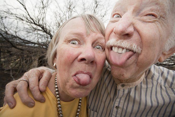 Pareja de adultos mayores sacando la lengua
