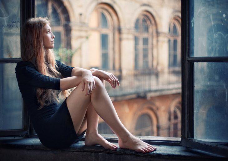Chica sentada en una ventana pensando