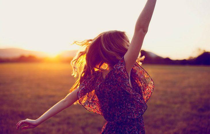 chica bailando al atardecer en el campo