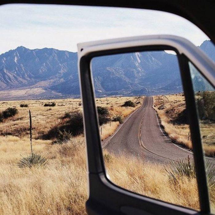 fotografía de carretera a través de la puerta de una camioneta