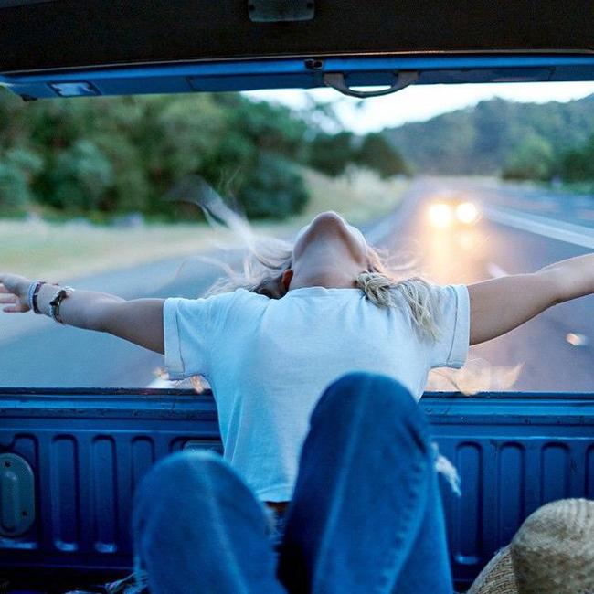 chica abre los brazos parte trasera camioneta