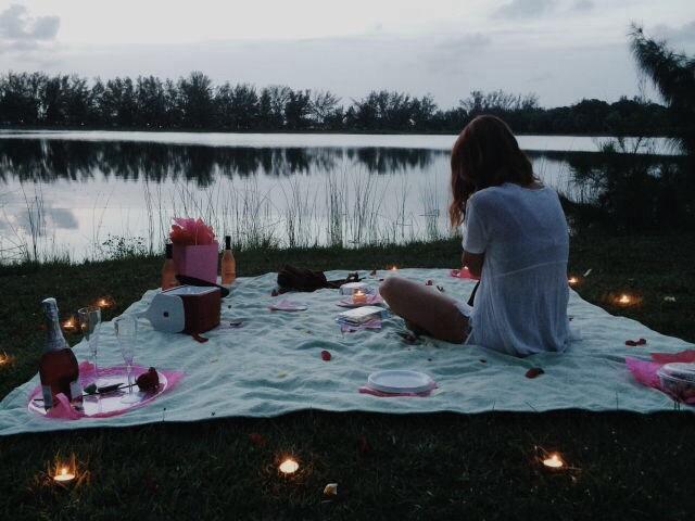 chica sobre frazada frente a lago