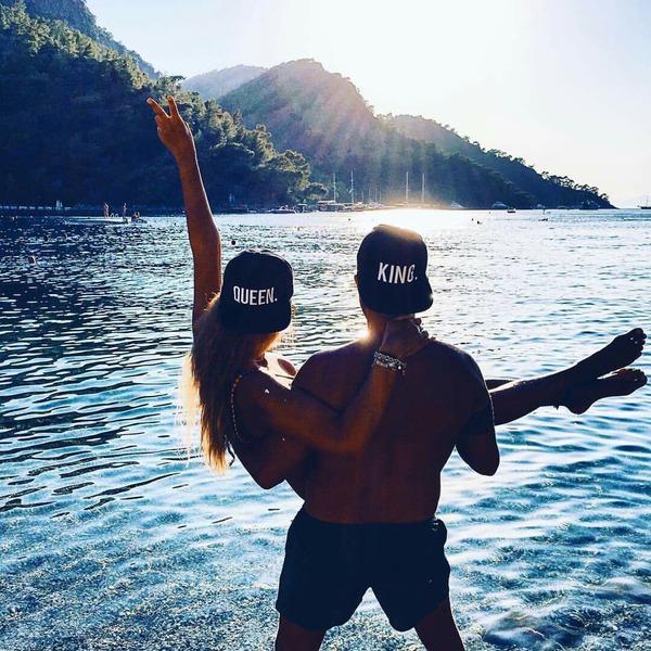 chico carga a chica en brazos frente a un lago