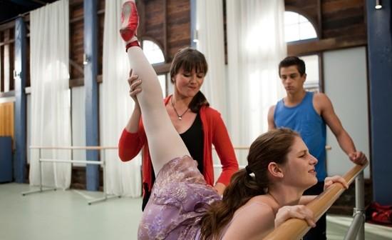 Chica bailarina de ballet practicando frente a una ventana