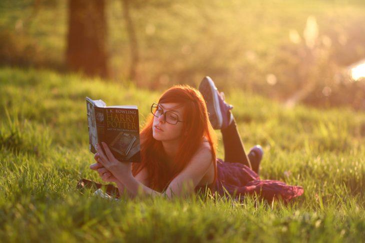 Chica recostada en el pasto leyendo el libro de Harry Potter